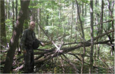 Dr. Burtsev next to structure allegedly built by Tennessee Bigfoot